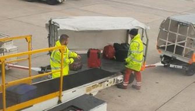 行李搬运工不小心扔箱子到购物车。信贷:Newsflare