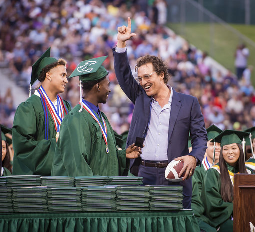 Kamden Perry, left, and Jephaniah Lister present actor Matthew McConaughey with an autographed football at the school's graduation ceremony. Credit: PA