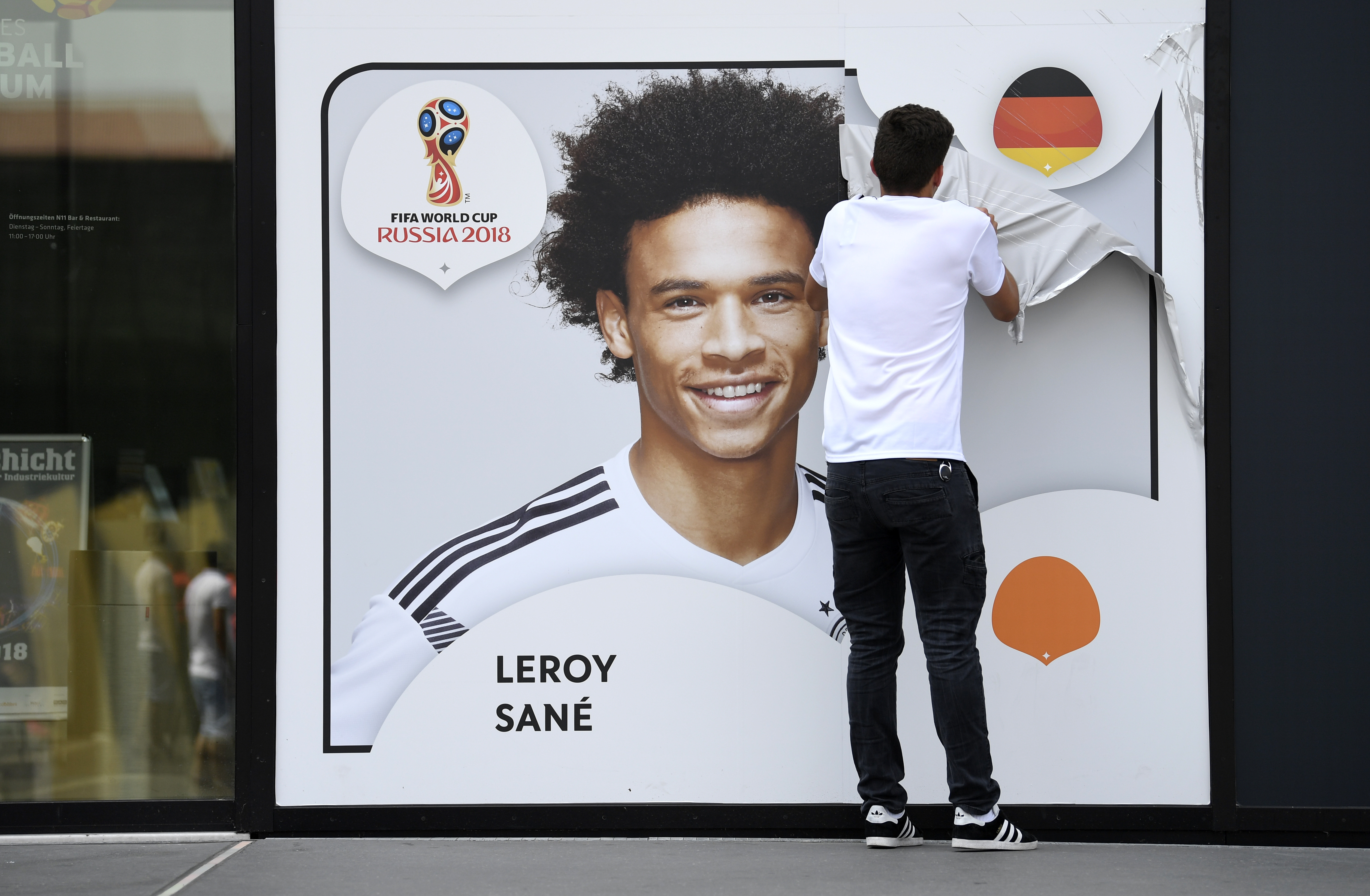 A worker peeling a picture of Leroy Sane off the wall of the German football museum. Image: PA