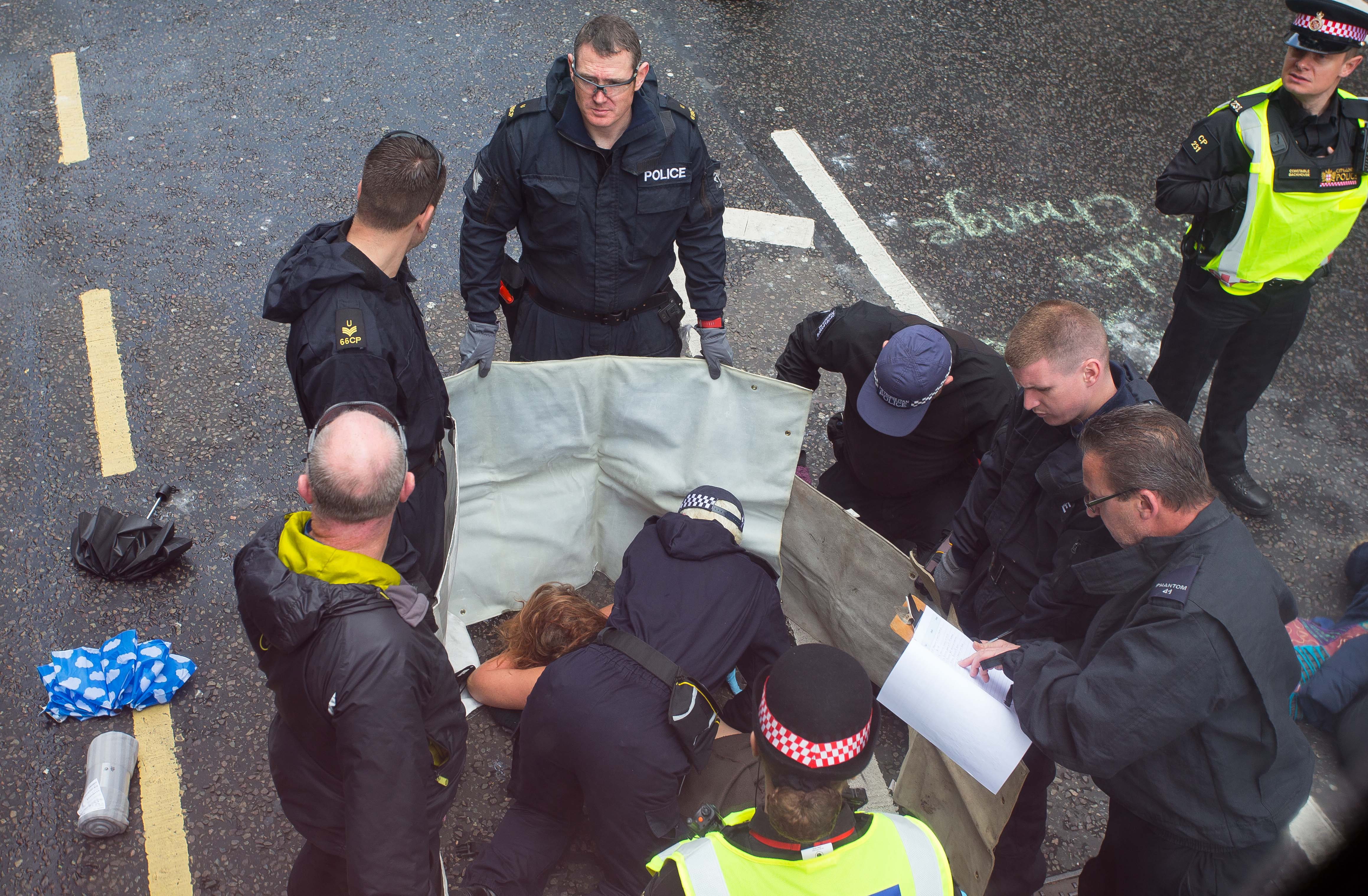 The woman was eventually removed from the road. Credit: Jamie Lorriman