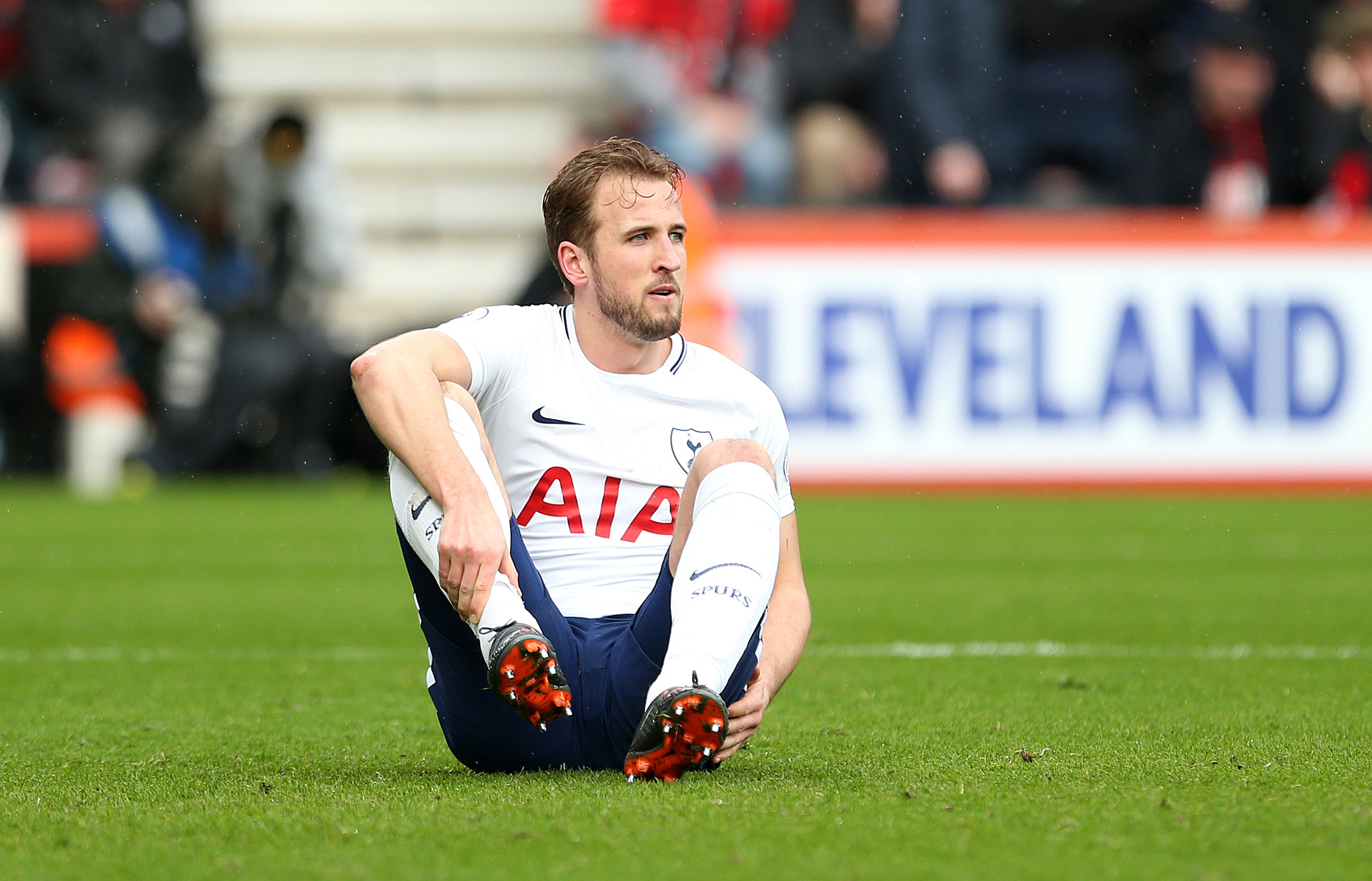 Kane sits on the pitch after suffering an injury. Image: PA
