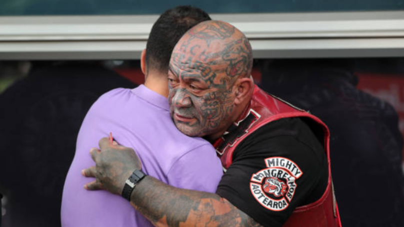 A gang member consoles mourners. Credit: Getty