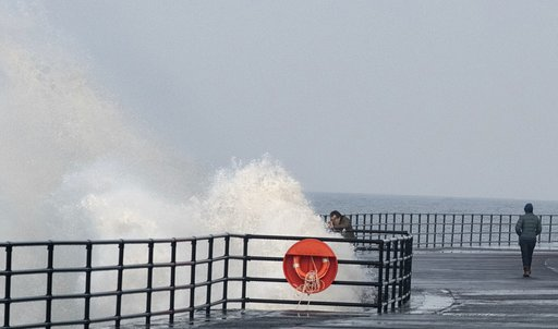 A man trying to take a selfie as the wave splashes him. Credit: Kennedy News and Media