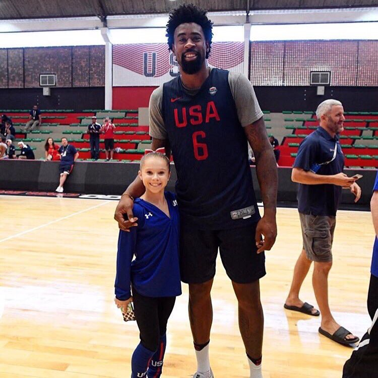 Olympic gymnast poses with a basketball player...