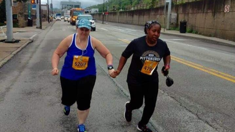 Marathon Runners Cross Finish Line Holding Hands As Final Competitors