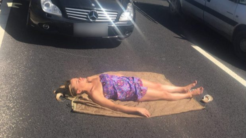 Woman Takes Advantage Of Traffic Jam To Indulge In A Spot Of Sunbathing