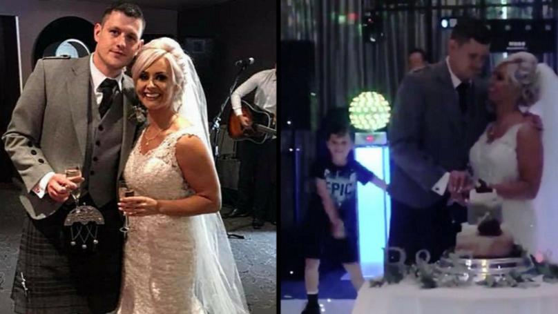 男孩自负的他新婚的父母使用牙线所切婚礼蛋糕