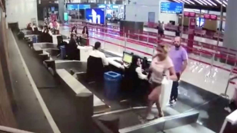 Woman Stands On Baggage Conveyor Belt At Airport And Immediately Stacks It