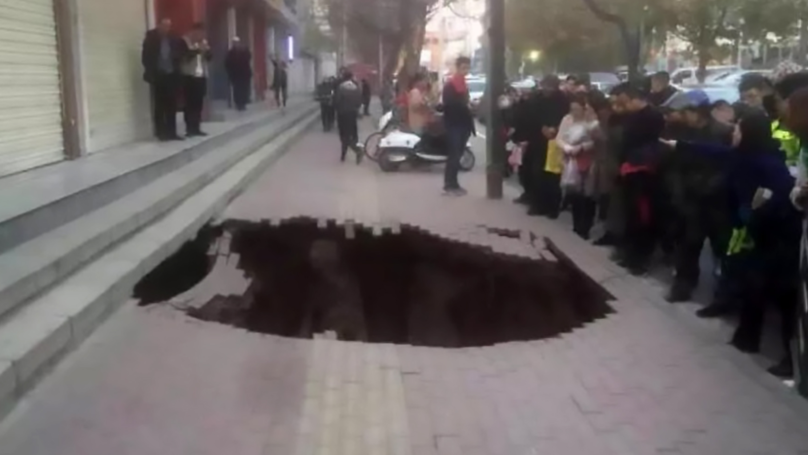 Woman Disappears Down Sinkhole As She Strolls Along Pavement