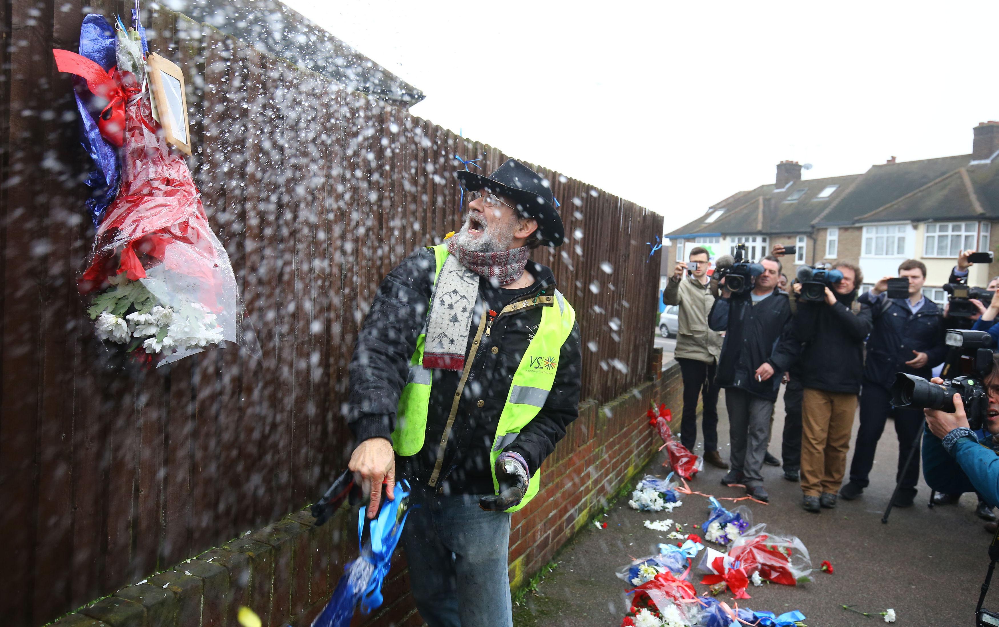 Vigilante Iain Gordon removes the flowers. Credit: PA