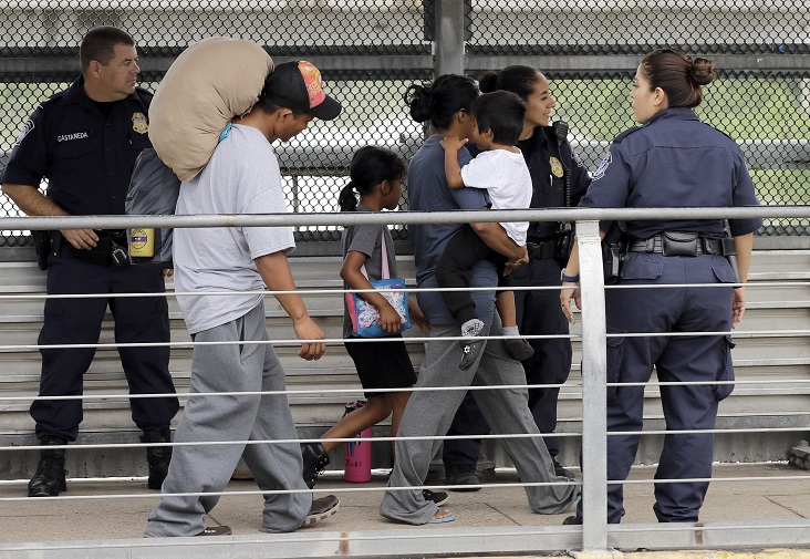 A family are escorted back across the border by U.S. Customs and Border Patrol agents. Credit: PA