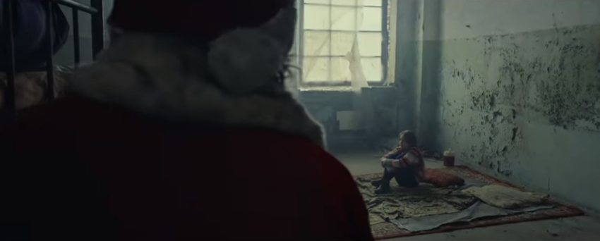 During the advert Santa finds a missing child in an abandoned building. (Credit: International Committee of the Red Cross)