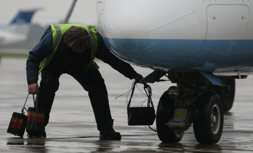 Stock photo of a member of airport staff attending to a plane. Credit: PA