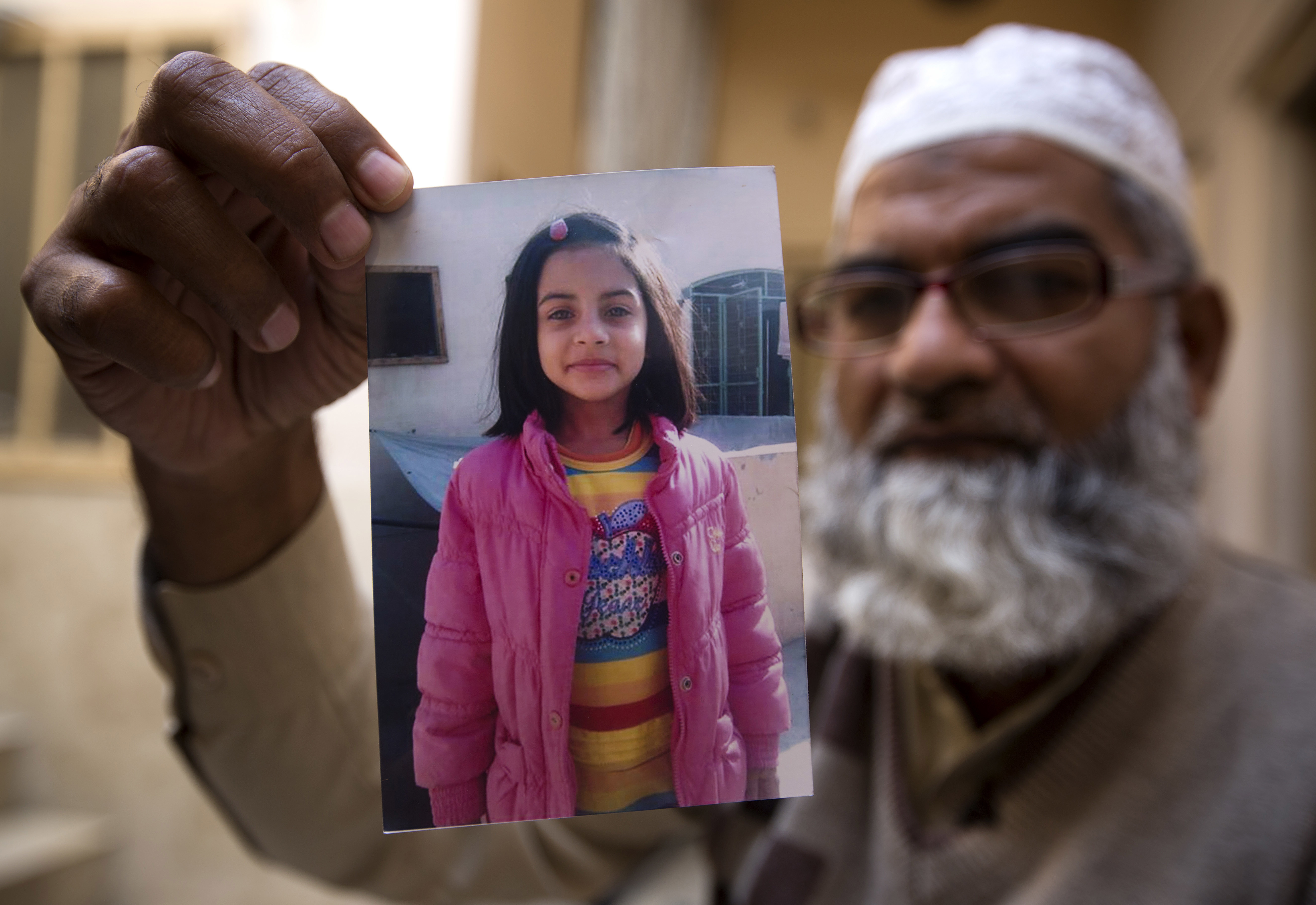 Mohammed Amin shows a picture of his daughter. Credit: PA