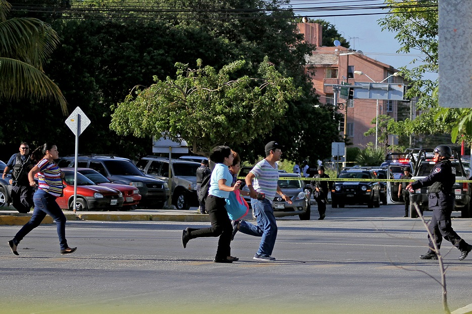 People running in the street following a shooting attack in Cancun. Credit: PA