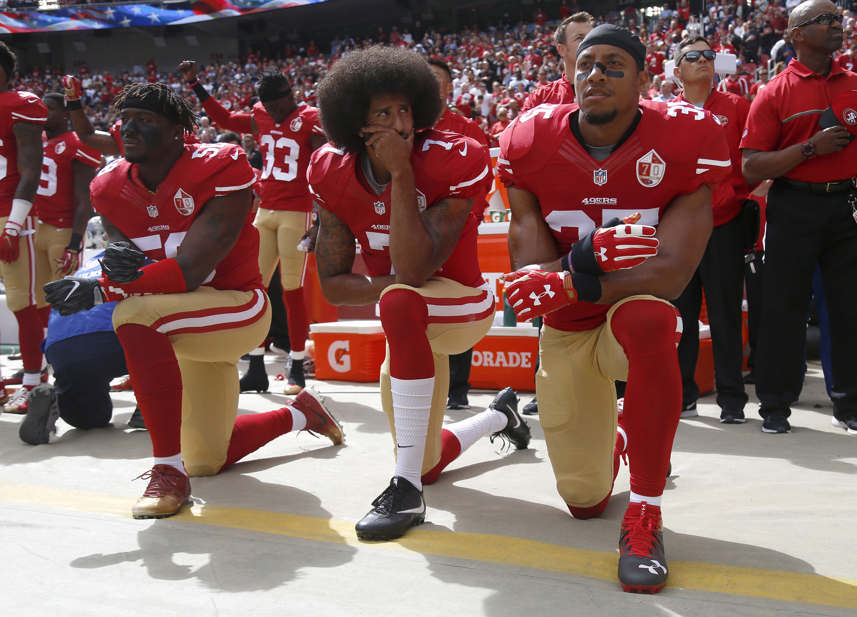 Colin Kaepernick and his teammates kneels in protest before an NFL game. Credit PA