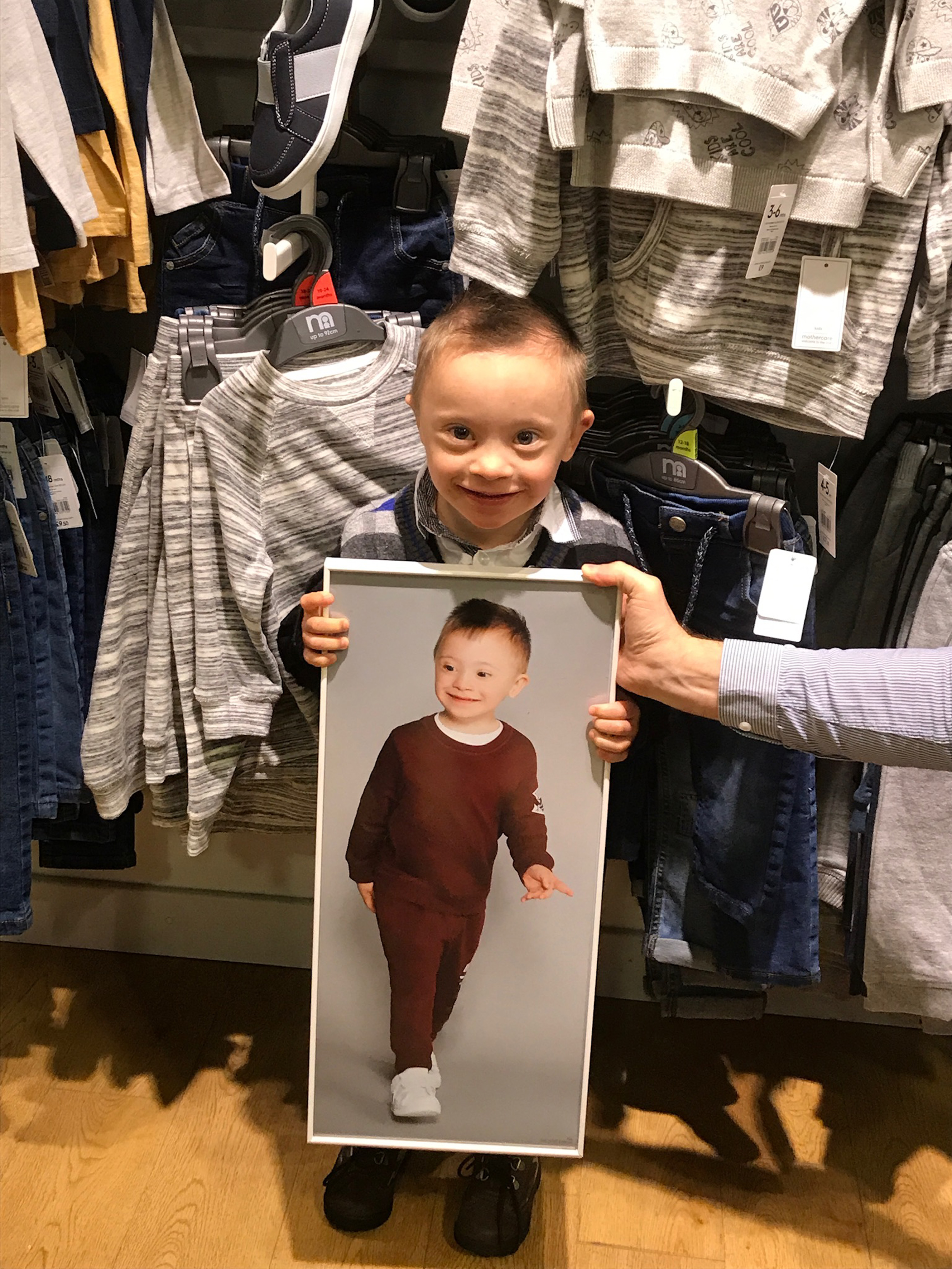 Riley proudly holding up his modelling image within a store . Credit: Caters