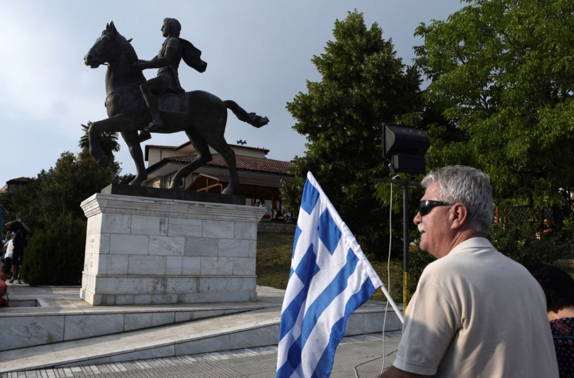 A man holds a Greek flag next to a statue of Alexander the Great. Credit PA