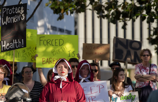Margeaux Hartline, dressed as a handmaid, protests against a ban on nearly all abortions outside of the Alabama State House. Credit: PA