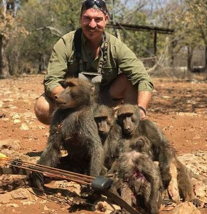 Wildlife official grins next to dead 'family of baboons' after slaughtering them